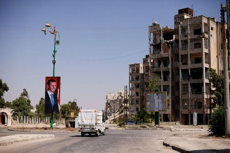 A picture of Syria's President Bashar al-Assad is seen in Waer district in the central Syrian city of Homs, Syria July 26, 2017. Picture taken July 26, 2017. REUTERS/Omar Sanadiki