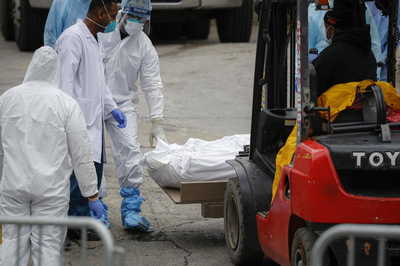 A body wrapped in plastic is prepared to be loaded onto a refrigerated container truck used as a temporary morgue by medical workers due to COVID-19 concerns, Tuesday, March 31, 2020, at Brooklyn Hospital Center in the Brooklyn borough of New York. The new coronavirus causes mild or moderate symptoms for most people, but for some, especially older adults and people with existing health problems, it can cause more severe illness or death. (AP Photo/John Minchillo)