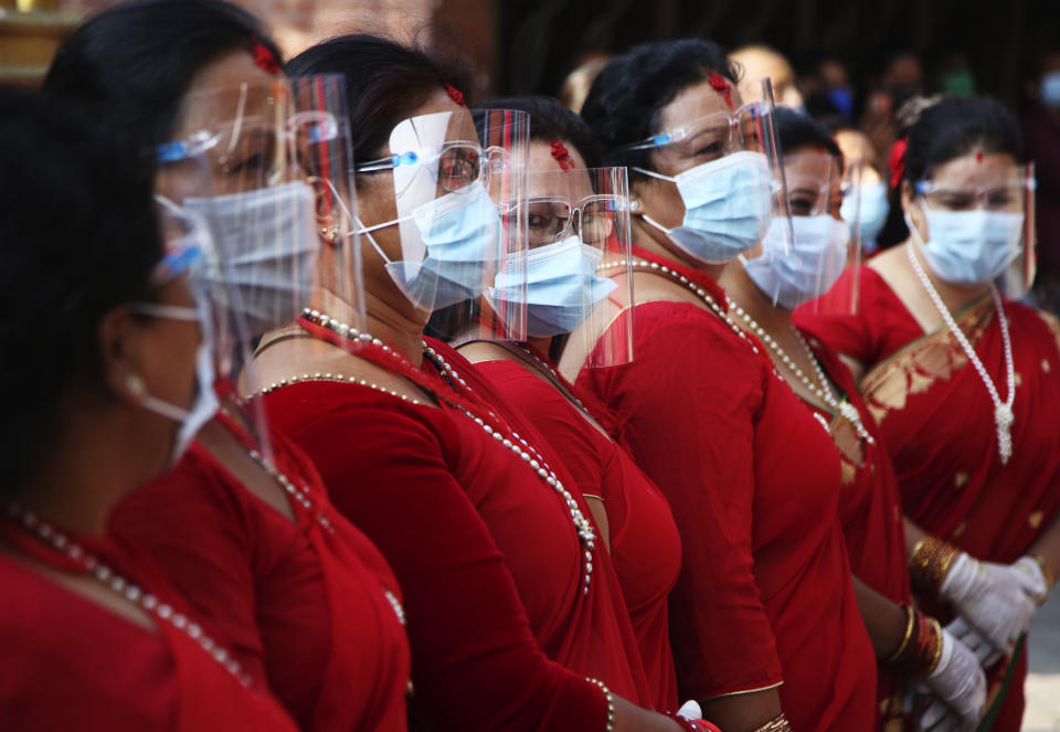 Nepalese devotees wearing protective gear as a precautionary measure against the coronavirus participate on Pachali Bhairav festival in Kathmandu, Nepal, Wednesday, Oct. 21, 2020. The festival which is usually celebrated in the night time during Dashain festival was celebrated during the day because of the pandemic. (AP Photo/Niranjan Shrestha)