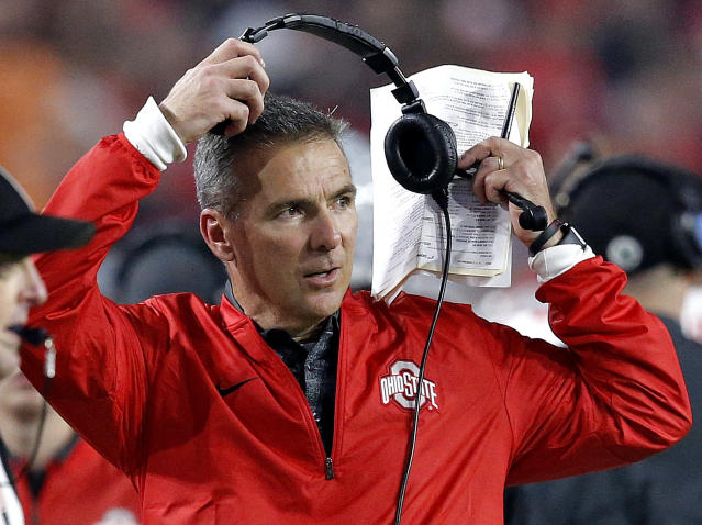 FILE – In this Dec. 31, 2016, file photo, Ohio State head coach Urban Meyer takes off his headset during the second half of the Fiesta Bowl NCAA college football game against Clemson, in Glendale, Ariz. A three-way quarterback derby promises to lend some intrigue to Ohio State's spring practice that opened on Tuesday, March 6, 2018. (AP Photo/Ross D. Franklin, File)