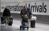 Travellers arrive at Heathrow Airport in London, Sunday, Jan. 17, 2021. The UK will close all travel corridors from Monday morning to protect against the coronavirus with travellers entering the country from overseas are required to have proof of a negative Covid test. (AP Photo/Frank Augstein)