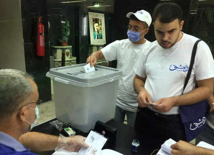A man wearing a face mask casts his vote inside a polling station during the parliamentary elections in Damascus