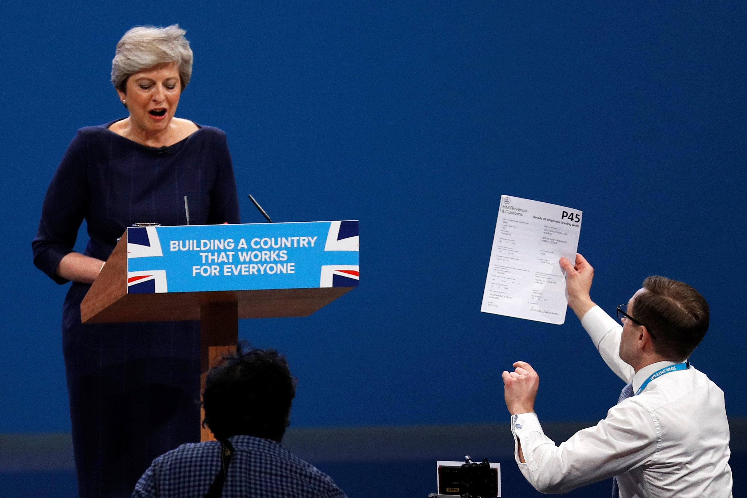 A member of the audience hands a P45 form (termination of employment tax form) to Britain's Prime Minister Theresa May as she addresses the Conservative Party conference in Manchester. (REUTERS/Phil Noble)