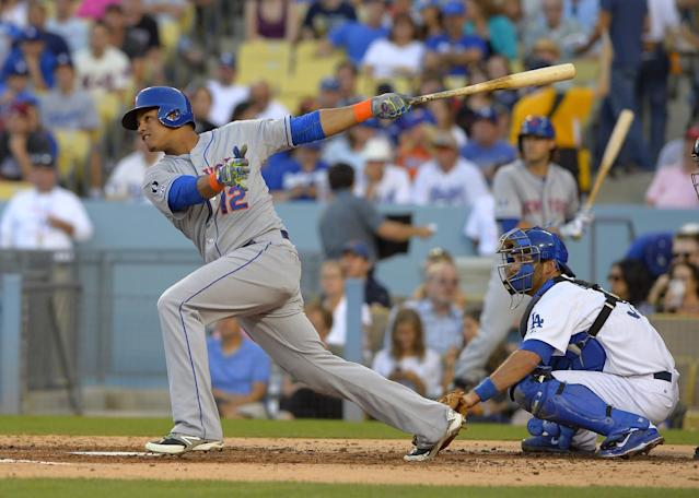 New York Mets' Juan Lagares follows through on a three-run home run in front of Los Angeles Dodgers catcher Drew Butera during the fourth inning of a baseball game, Saturday, Aug. 23, 2014, in Los Angeles. (AP Photo/Mark J. Terrill)