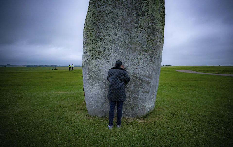 A man touches one of the standing stones during Summer Solstice at Stonehenge, where some people jumped over the fence to enter the stone-circle to watch the sun rise at dawn of the longest day of the year in the UK, in Amesbury, England, Monday June 21, 2021. The prehistoric monument of ancient stones have been officially closed for the celebrations due to the coronavirus lockdown, but groups of people ignored the lockdown to mark the Solstice, watched by low key security. (Ben Birchall/PA via AP)
