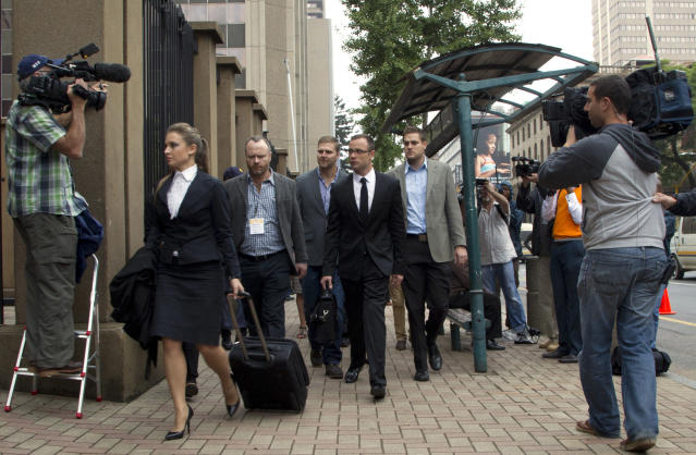 Oscar Pistorius, middle, accompanied by relatives arrives at the high court in Pretoria, South Africa, Friday, March 14, 2014. Pistorius is charged with murder for the shooting death of his girlfriend, Reeva Steenkamp, on Valentines Day in 2013. (AP Photo/Themba Hadebe)