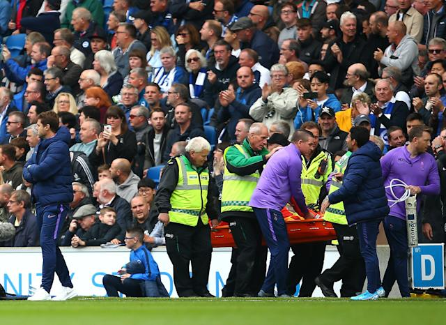 Hugo Lloris is taken off on a stretcher, passing Mauricio Pochettino. (Photo by Charlie Crowhurst/Getty Images)