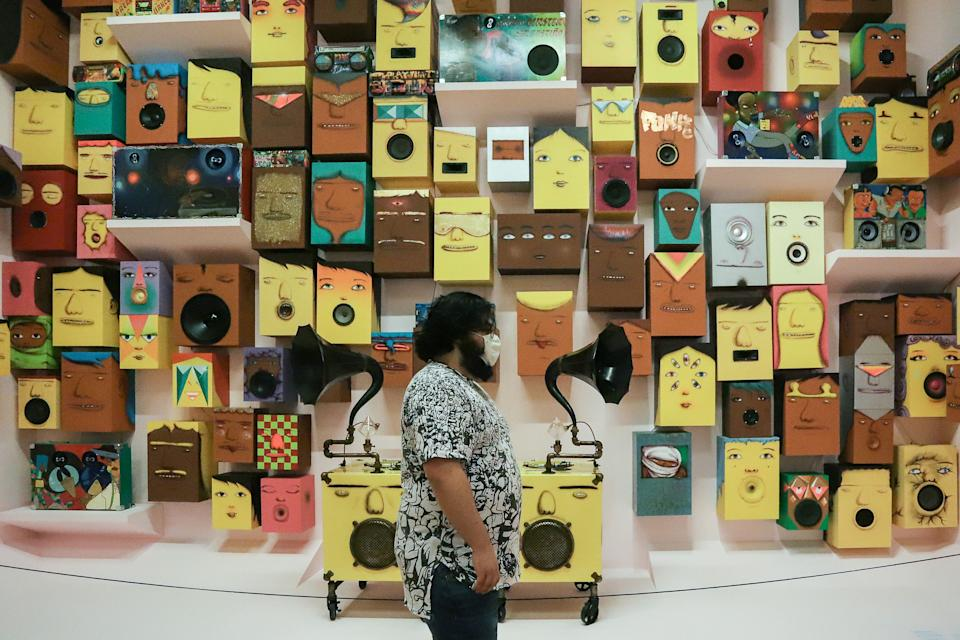 """SAO PAULO, Oct. 15, 2020 -- A visitor appreciates artworks of Brazilian artists """"Os Gemeos"""" at the reopened Pinacoteca museum amid COVID-19 outbreak, in Sao Paulo, Brazil on Oct. 15, 2020. (Photo by Rahel Patrasso/Xinhua via Getty) (Xinhua/Rahel Patrasso via Getty Images)"""