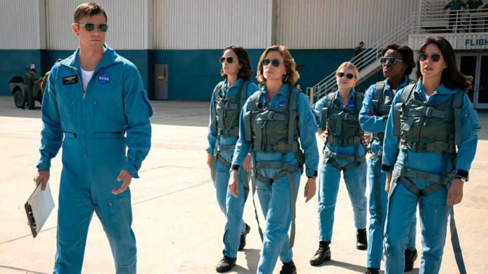 A man in a blue pilot jumpsuit leads a group of five women in similar suits