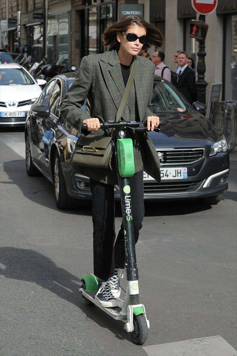 """<p>The model was spotted darting about in Paris on a scooter, wearing a paired down look with the new Alexander McQueen<a href=""""https://www.elle.com/uk/fashion/g21202204/designer-bags-we-want-to-splash-our-cash-on/?slide=2"""" rel=""""nofollow noopener"""" target=""""_blank"""" data-ylk=""""slk:Story bag"""" class=""""link rapid-noclick-resp""""> Story bag</a>. </p>"""