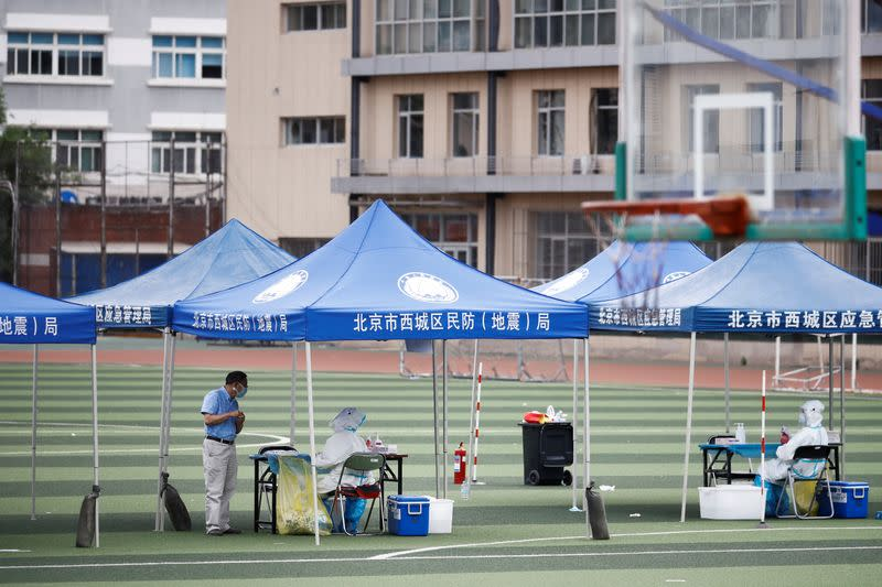 Medical staff wait for people to get tested for the coronavirus at the Guangan Sport Center after an unexpected spike of cases of the coronavirus disease (COVID-19) in Beijing
