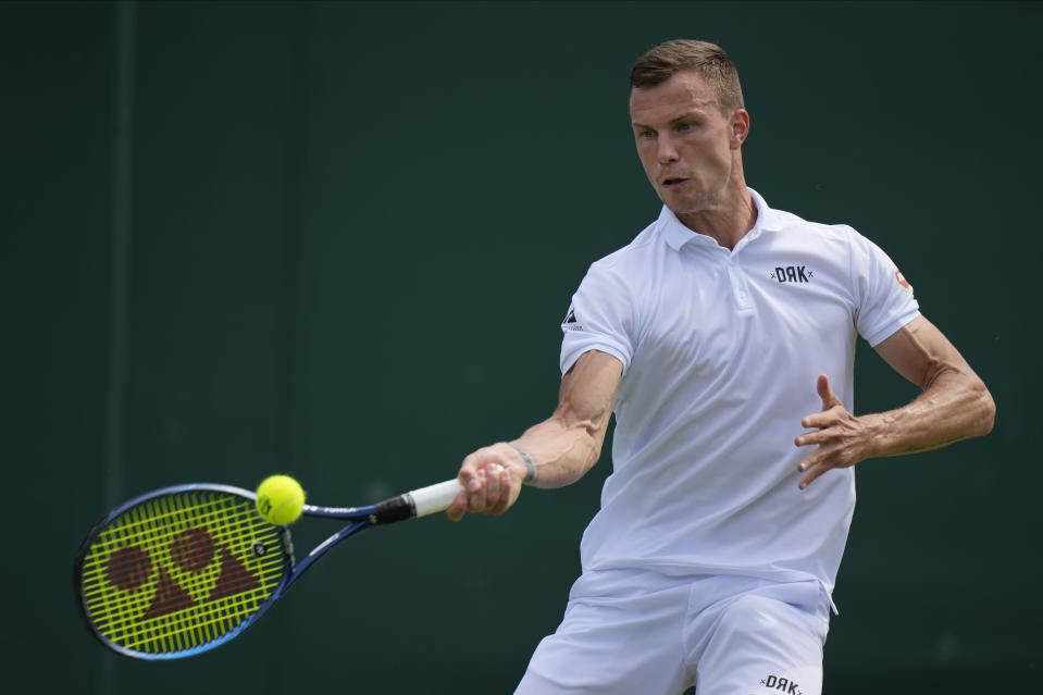 Hungary's Marton Fucsovics plays a return to Argentina's Diego Schwartzman during the men's singles third round match on day five of the Wimbledon Tennis Championships in London, Friday July 2, 2021. (AP Photo/Alastair Grant)