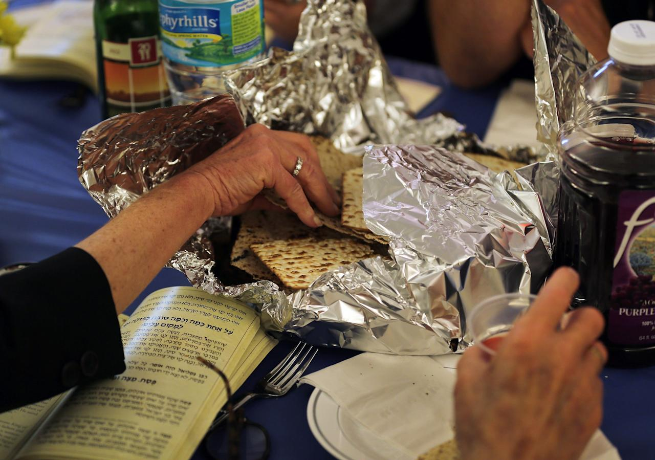MIAMI BEACH, FL - MARCH 25: People take part in eating matzo during a community Passover Seder at Beth Israel synagogue  on March 25, 2013 in Miami Beach, Florida. The community Passover Seder that served around 150 people has been held for the past 30 years and is welcome to anyone in the community that wants to commemorate the emancipation of the Israelites from slavery in ancient Egypt.  (Photo by Joe Raedle/Getty Images)