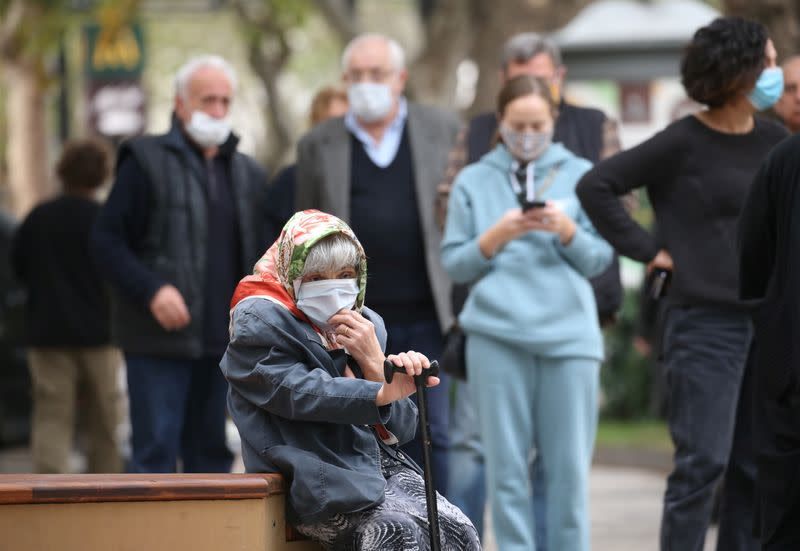An elderly woman sits as she waits outside a polling station during a parliamentary election in Tbilisi