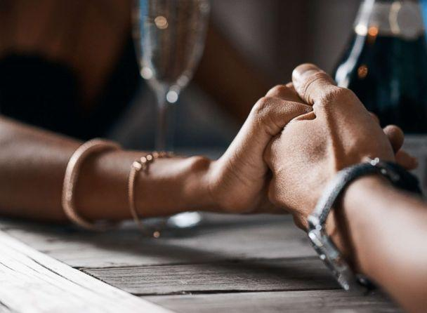 PHOTO: A stock photo of a couple holding hands at a table. (STOCK PHOTO/Getty Images)