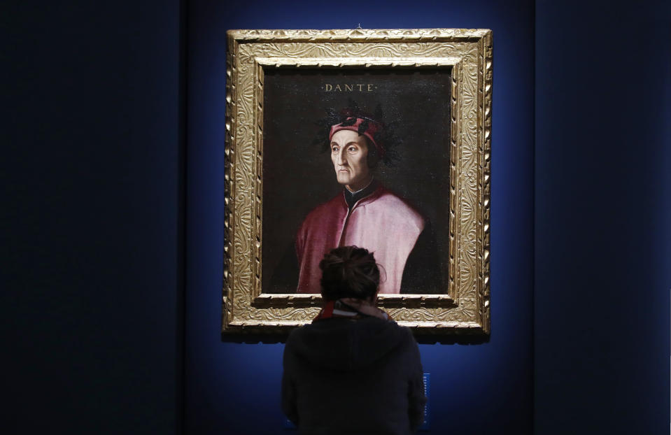 """A woman looks at a portrait of poet Dante Alighieri, by an 18th century Florentine anonymous painter, at the """"Dante. La visione dell'arte"""" (Dante. The Vision of Art) exhibition, in Forli, Italy, Saturday, May 8, 2021. Italy is honoring its great poet in myriad ways on the 700th anniversary of his death, with new musical scores and gala concerts, exhibits and dramatic readings against stunning backgrounds in every corner of the land. (AP Photo/Antonio Calanni)"""