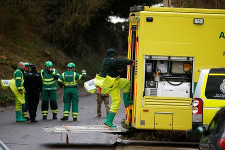 Members of the emergency services wearing protective suits work at a site in Winterslow, near Salisbury