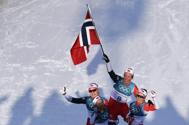 Cross-Country Skiing - Pyeongchang 2018 Winter Olympics - Women's 30km Mass Start Classic - Alpensia Cross-Country Skiing Centre - Pyeongchang, South Korea - February 25, 2018 - Winner Marit Bjoergen of Norway waves the Norwegian flag as she is carried by her teammates. REUTERS/Toby Melville