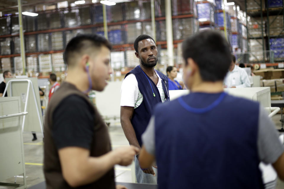 FILE - Rodin St. Surin, of Haiti, looks on as coworkers talk on the floor of a factory Monday, June 6, 2017, in Tijuana, Mexico. Though Haitians living in the U.S. rejoiced when a recent extension was granted, Homeland Security Secretary Alejandro Mayorkas pointedly noted that it doesn't apply to Haitians outside the U.S. and said those who enter the country may be flown home. That means bleak choices for many Haitians who fled Haiti sometime after a 2010 earthquake, initially escaping to South America and later to Mexican cities that border the United States. (AP Photo/Gregory Bull)