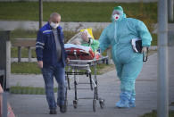 Medical workers carry a patient suspected of having coronavirus on a stretcher at a hospital in Kommunarka, outside Moscow, Russia, Monday, Oct. 11, 2021. Russia's daily coronavirus infections and deaths are hovering near all-time highs amid a laggard vaccination rate and the Kremlin's reluctance to toughen restrictions. Russia's state coronavirus task force reported 29,409 new confirmed cases Monday. That's the highest number since the start of the year and just slightly lower than the pandemic record reached in December. (AP Photo/Alexander Zemlianichenko)