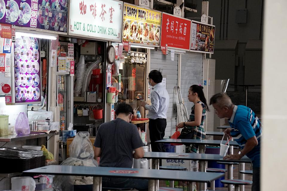 A man in a face mask ordering food at the Amoy Street Food Centre on 7 April 2020, the first day of Singapore's month-long circuit breaker period. (PHOTO: Dhany Osman / Yahoo News Singapore)