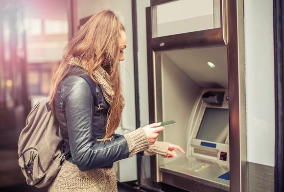 Young woman with backpack standing at ATM making withdrawal