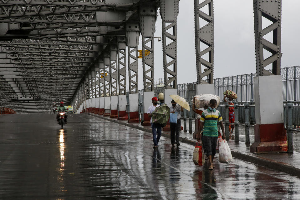 Commuters walk along the city's iconic landmark, Howrah Bridge to cross the Hooghly River as it rains in Kolkata, India, Wednesday, May 20, 2020. Amphan, a powerful cyclone has slammed ashore along the coastline of India and Bangladesh where more than 2.6 million people fled to shelters in a frantic evacuation made all the more challenging by the coronavirus pandemic. (AP Photo/Bikas Das)