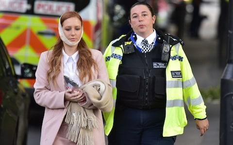 An injured woman is assisted by a police officer close to Parsons Green station - Credit: Dominic Lipinski/PA