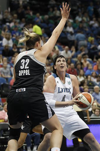 Minnesota Lynx forward Janel McCarville (4) looks up to the basket against the defense of San Antonio Silver Stars center Jayne Appel (32) in the first half of a WNBA basketball game, Tuesday, June 11, 2013, in Minneapolis. (AP Photo/Stacy Bengs)