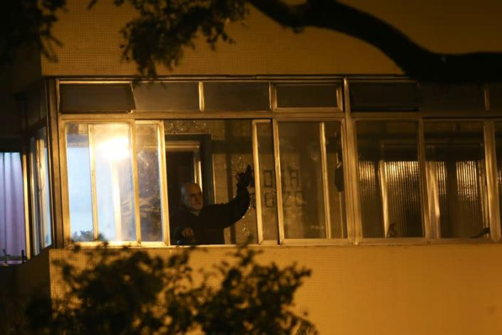 A demonstrators hits a pot lid as protest against Brazilian President Jair Bolsonaro's televised speech from the window of their home during the outbreak of the coronavirus disease (COVID-19) in Sao Paulo