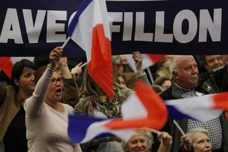 Supporters of Francois Fillon, former French prime minister and member of Les Republicains political party, wave flags as they attend a campaign rally in the second round for the French center-right presidential primary election in Paris, France, November 25, 2016.  REUTERS/Philippe Wojazer