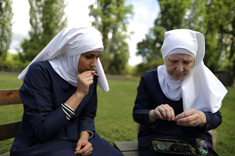 """California """"weed nun"""" Christine Meeusen, 57, (R), and India Delgado, who goes by the name Sister Eevee, smoke a joint at Sisters of the Valley near Merced, California, U.S., April 18, 2017. Picture taken April 18, 2017. REUTERS/Lucy Nicholson"""