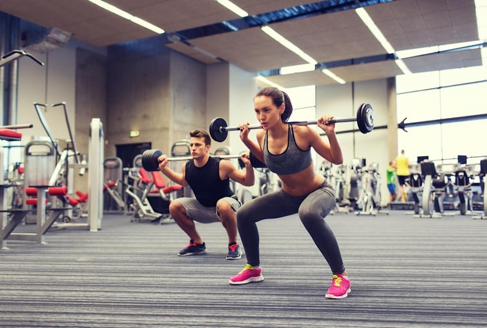 young man and woman with barbell flexing muscles and making shoulder press squat in gym