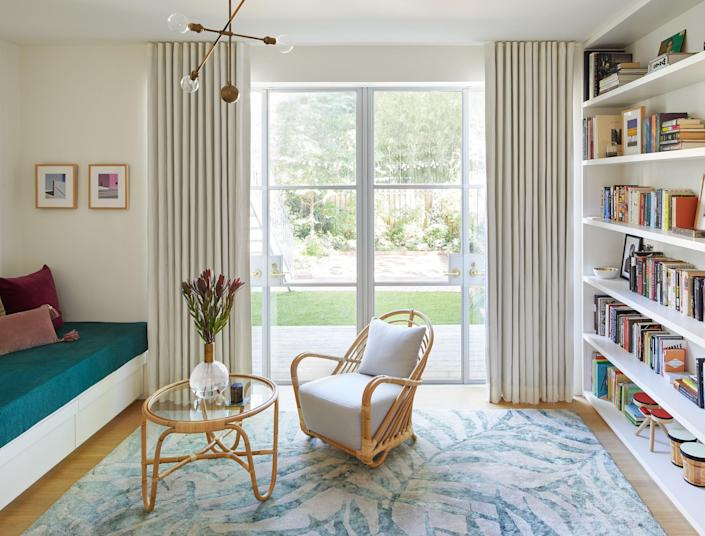 Here on the first floor, in the garden room, the custom built-in daybed is upholstered in dark green linen from Cloth Fabric; the Charlottenborg chair and table are by Arne Jacobsen; and the light fixtures are by Apparatus Studio.