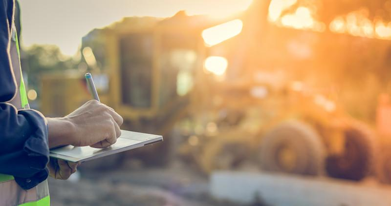 A person holding a tablet near a construction site with a bright sun in the background.