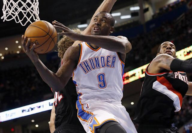 Oklahoma City Thunder forward Serge Ibaka (9) shoots in front of Portland Trail Blazers center Robin Lopez (42) and forward LaMarcus Aldridge (12) in the third quarter of an NBA basketball game in Oklahoma City, Tuesday, Jan. 21, 2014. Oklahoma City won 105-97. (AP Photo/Sue Ogrocki)