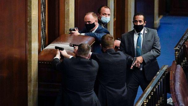 PHOTO: U.S. Capitol Police with guns drawn stand near a barricaded door as protesters try to break into the House Chamber at the U.S. Capitol, Jan. 6, 2021, in Washington, D.C. (Andrew Harnik/AP)