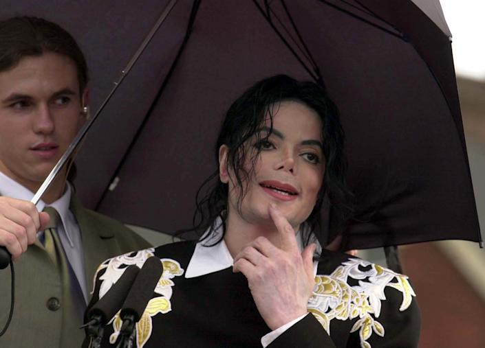Michael Jackson, shielded from the rain by bodyguard Matt Fiddes, attends a fundraising event at Exeter Football Club in 2002.