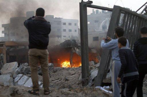<p>Palestinians take photographs of destruction after Israeli air strikes in Gaza City on November 19, 2012. An Israeli air strike early on Monday killed three Palestinians in a car in central Gaza, medics said, raising the toll to 85 as Israel's relentless air campaign entered its sixth day.</p>