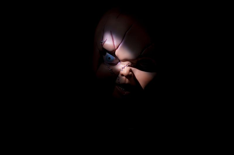 Close-Up Of Sewed Chucky Toy Against Black Background