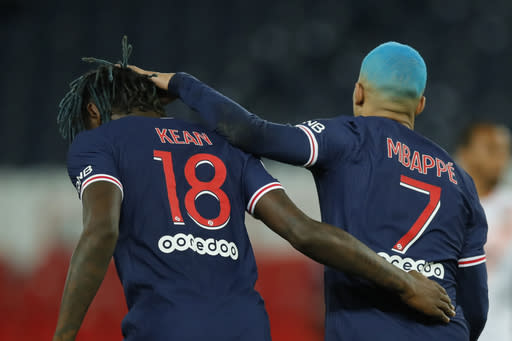 PSG's Kylian Mbappe, right celebrates with PSG's Moise Kean after scoring during the French League One soccer match between Paris Saint-Germain and Lorient at the Parc des Princes in Paris, France, Wednesday, Dec. 16, 2020. (AP Photo/Christophe Ena)