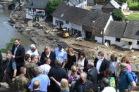 German Chancellor Angela Merkel, rear third left, and the Governor of the German state of Rhineland-Palatinate, Malu Dreyer, rear fifth left, are seen on a bridge in Schuld, western Germany, Sunday, July 18, 2021 during their visit in the flood-ravaged areas to survey the damage and meet survivors. After days of extreme downpours causing devastating floods in Germany and other parts of western Europe the death toll has risen. (Christof Stache/Pool Photo via AP)