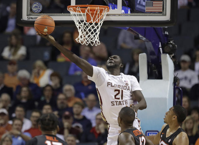 Florida State's Christ Koumadje (21) drives to the basket against Virginia Tech during the first half of an NCAA college basketball game in the Atlantic Coast Conference tournament in Charlotte, N.C., Thursday, March 14, 2019. (AP Photo/Chuck Burton)
