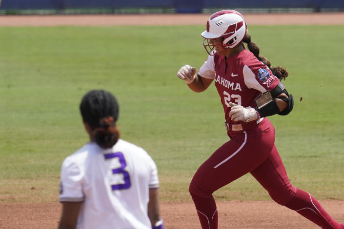 Oklahoma's Tiare Jennings, right, runs past James Madison pitcher Odicci Alexander (3) with a home run in the first inning of an NCAA Women's College World Series softball game Sunday, June 6, 2021, in Oklahoma City. (AP Photo/Sue Ogrocki)