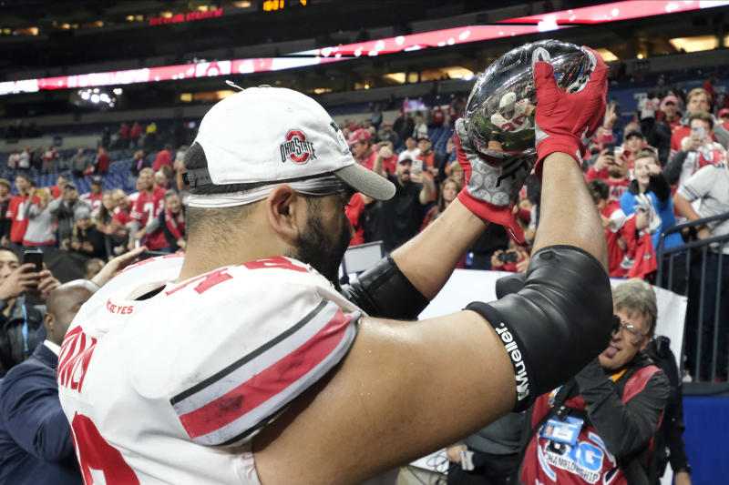 Ohio State offensive lineman Branden Bowen (76) holds the trophy as he leaves the field following the team's 34-21 win over Wisconsin in the Big Ten championship NCAA college football game, early Sunday, Dec. 8, 2019, in Indianapolis. (AP Photo/AJ Mast)