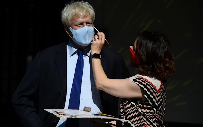 An artist puts the finishing touches to a wax figure of Prime Minister Boris Johnson, in the entrance line at Madame Tussaud's - Kirsty O'Connor /PA