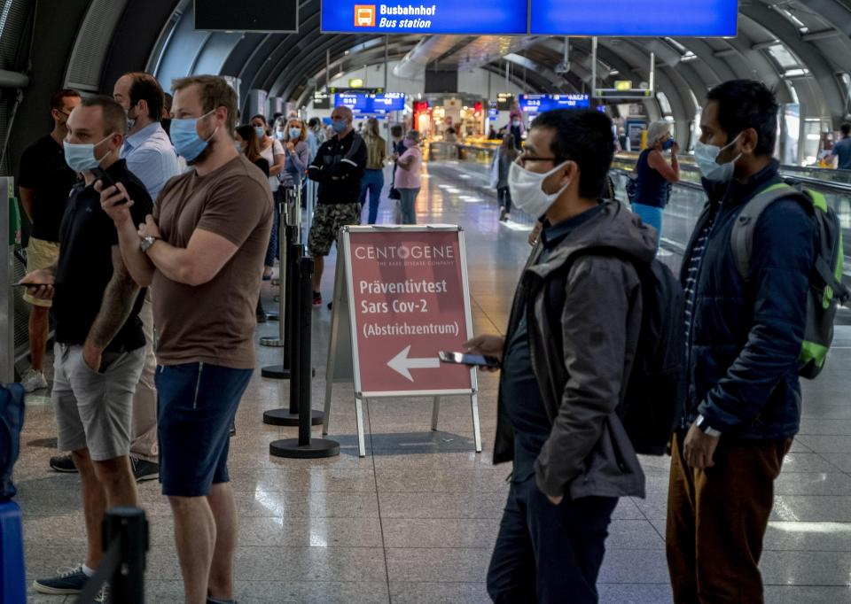 Dozens of passengers from various countries queue at the Centogene test center for a Covid-19 test at the airport in Frankfurt, Germany, Friday, July 24, 2020. (AP Photo/Michael Probst)
