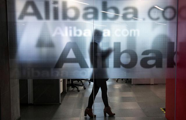 FILE PHOTO: An employee is seen behind a glass wall with the logo of Alibaba at the company's headquarters on the outskirts of Hangzhou, Zhejiang province, April 23, 2014. REUTERS/Chance Chan/File Photo