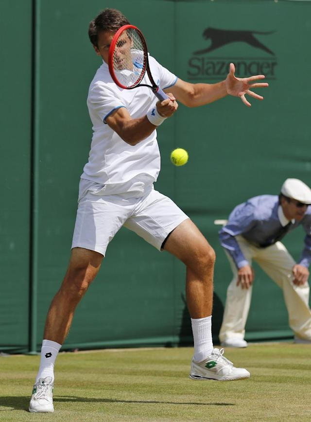 Sergiy Stakhovsky of Ukraine plays a return to Ernests Gulbis of Latvia during their men's single match at the All England Lawn Tennis Championships in Wimbledon, London, Wednesday, June 25, 2014. (AP Photo/Ben Curtis)