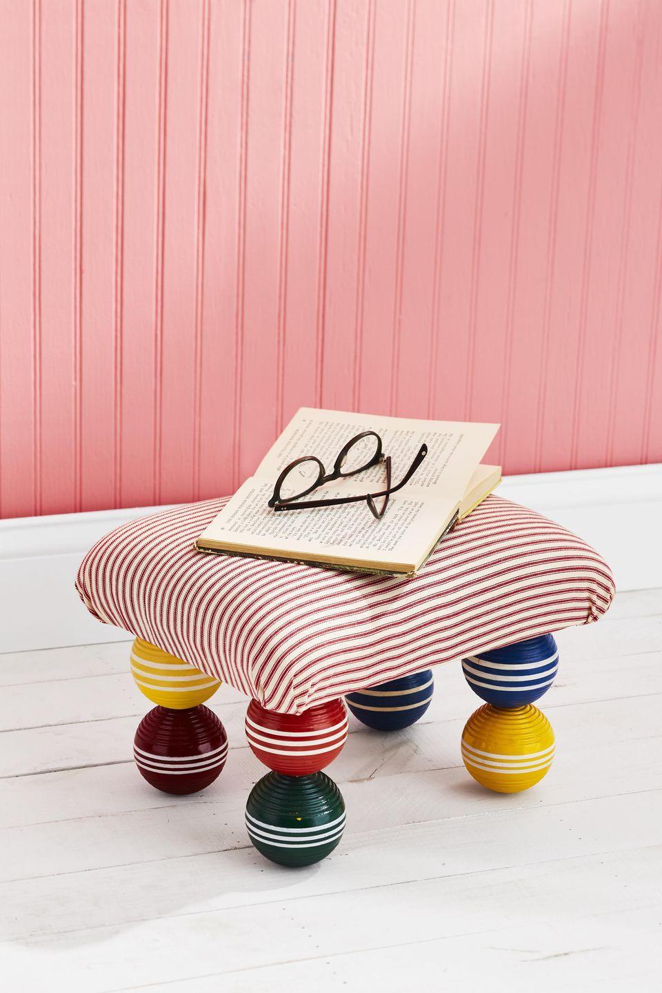 <p>Customize this sweet footstool by using all one color or maybe two croquet balls and covering the top with a fabric that matches your already existing color scheme.<strong><br></strong></p><p><strong>To make: </strong>Cut a piece of plywood into a 13 1/2-by-11-inch rectangle. Drill a 5/8-inch hole 2 inches deep in eight croquet balls. Glue one ball, hole side down, 2 1/4 inches from each corner of plywood. Cut a 5/8-inch dowel into 4 four-inch-long pieces. Glue one length in each unused ball. Thread dowels into balls attached to board, gluing in place. Cover wood with batting and fabric. Secure in place with a staple gun.</p>
